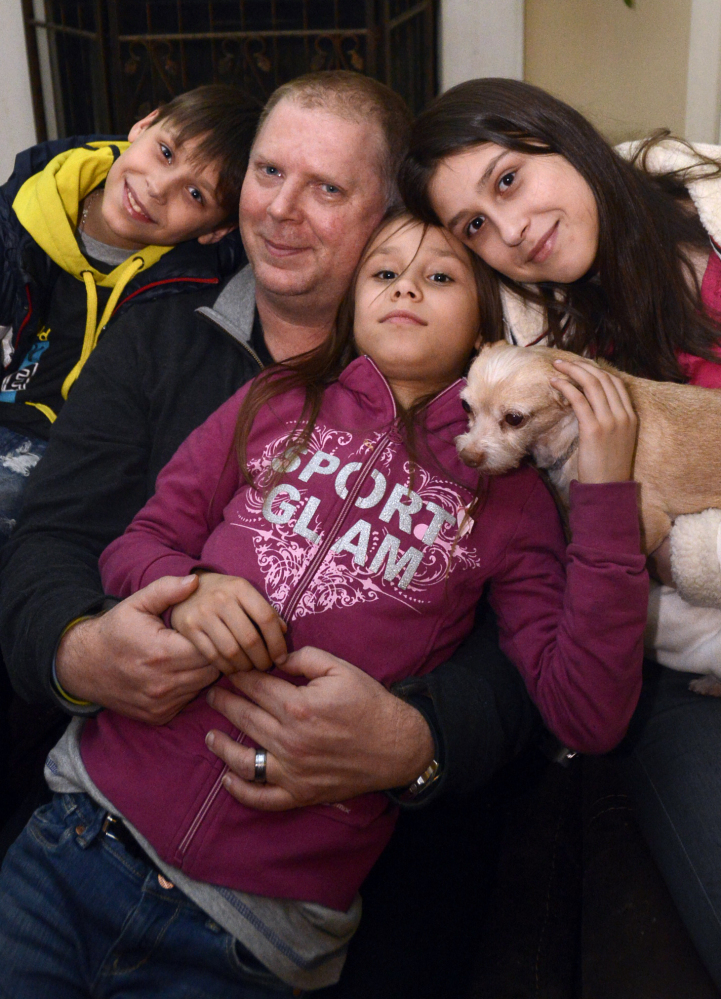 David Bundy sits with his newly adopted children, Max, 11, from left, Alla, 9, and Karina, 14. He headed home to Montgomery, Ala., early with the children to escape the violence.