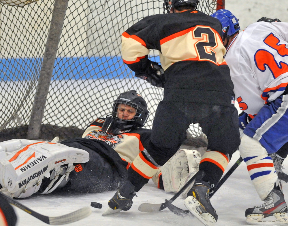 Brunswick goalie Blake Alexander keeps his eye on a loose puck as Brady Martin, right, of Lawrence/Skowhegan looks to get the rebound while being defended by Matt Brooks of Brunswick. Brooks scored in a 1-0 victory.