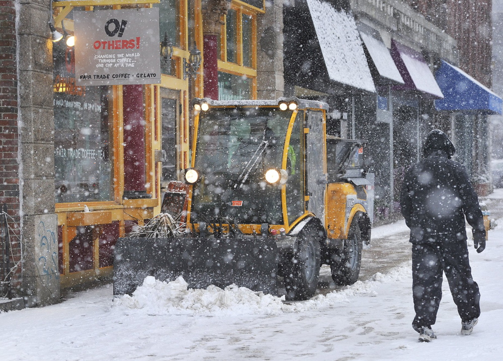 One of the city's sidewalk plows clears a path for pedestrians in Portland's Monument Square during a sudden snow squall on January 18.