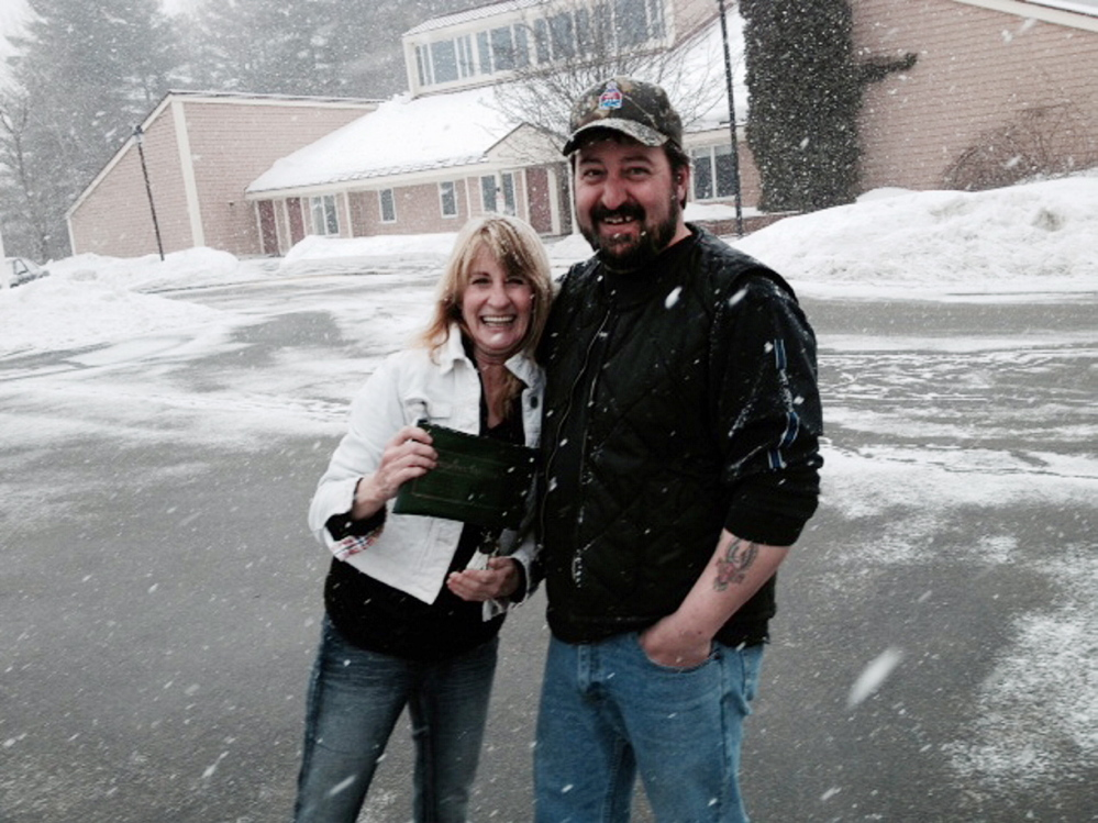 paying it forward: Cathy Landry gives Mark Isbell a hug Wednesday after he shows her where he found her bank bag containing $1,500 cash off Louise Avenue in Waterville.