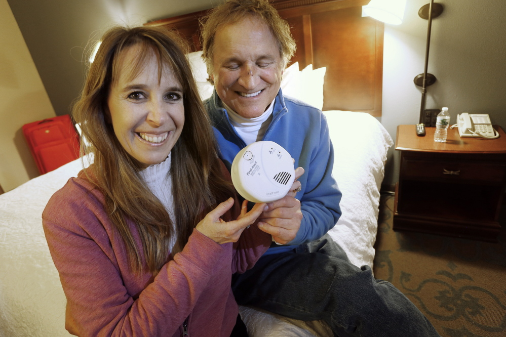 John Yates and Lori Blackwell of Southbury, Conn., in their hotel room in Wells on Wednesday, show a plug-in carbon monoxide detector they purchased Sunday after becoming ill from the gas at an Ogunquit resort.