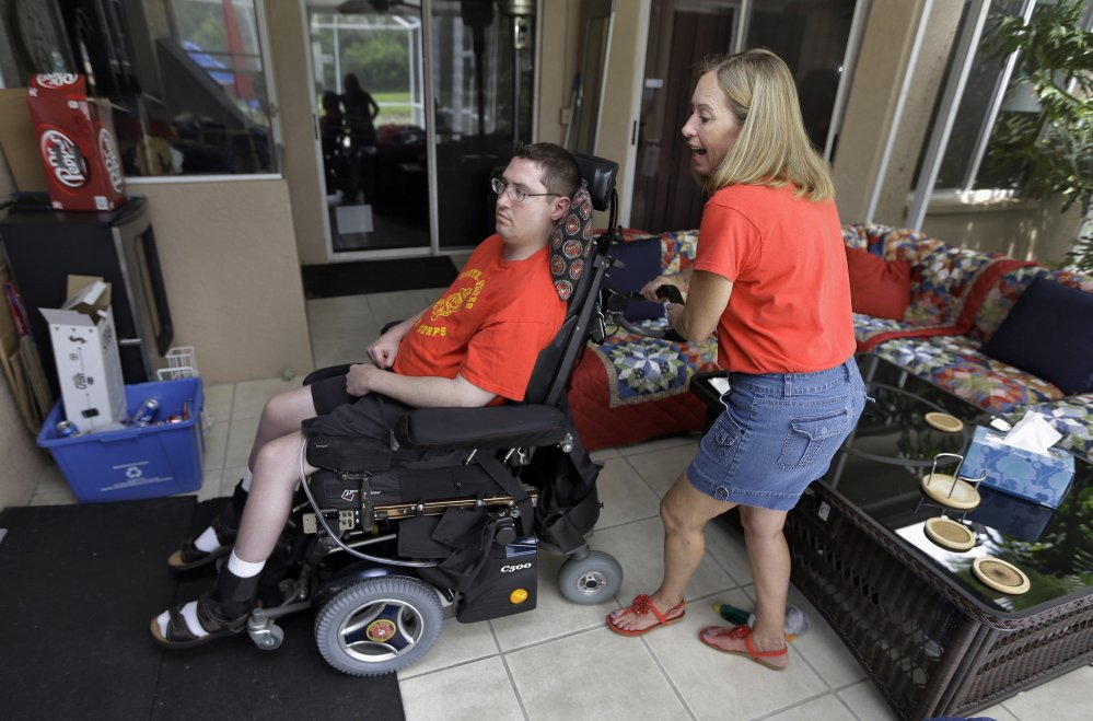 Chris Ott helps her son, former Marine John Thomas Doody, who was shot while serving in Fallujah, Iraq, in Riverview, Fla. More than two dozen veterans' groups supported legislation rejected in the Senate on Thursday to boost aid to veterans.