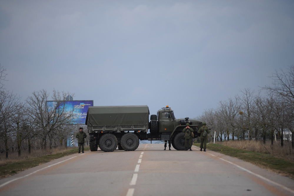Russian troops block the road to the military airport at the Black Sea port of Sevastopol in Crimea, Ukraine, Friday. Heightened security is evident with Russian military around Sevastopol, the location for Russia military bases.