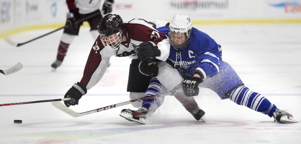 Shawn Sullivan, left, of Gorham and Bryce Fraser of Kennebunk get tangled while battling for the puck Friday night during a Western Class B boys' hockey semifinal at the Colisee in Lewiston.