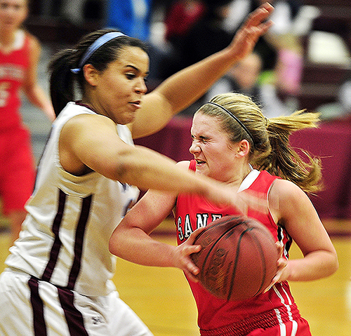 Lonnie Staten of Windham, left, attempts to strip the ball from Summer Camire of Sanford during their Western Class A prelim game Wednesday night. Windham won 35-23 and will meet Thornton Academy next.