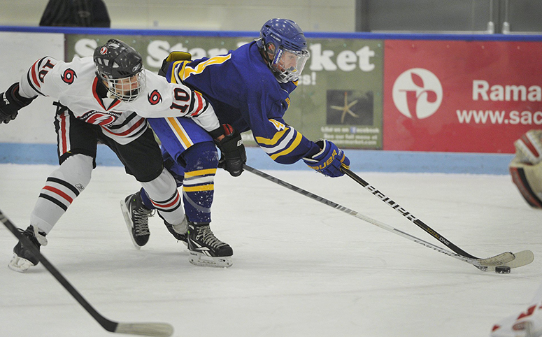 Falmouth's Tyler Jordan, No. 4, tries to move the puck around the defense of Scarborough's Cam Nigro, No. 10, in this Dec. 9, 2013, game played at the at the University of New England.