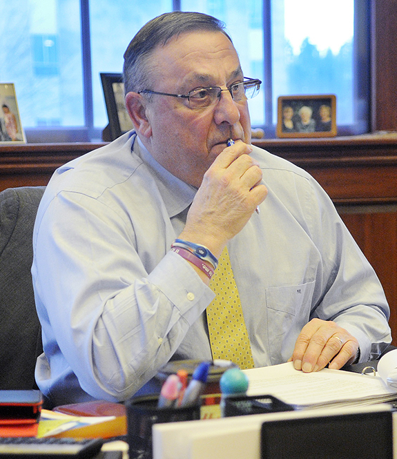 Gov. Paul LePage listens to an aide discuss a revision to his third State of the State address Monday during a meeting to compose the speech in the governor's office in Augusta.