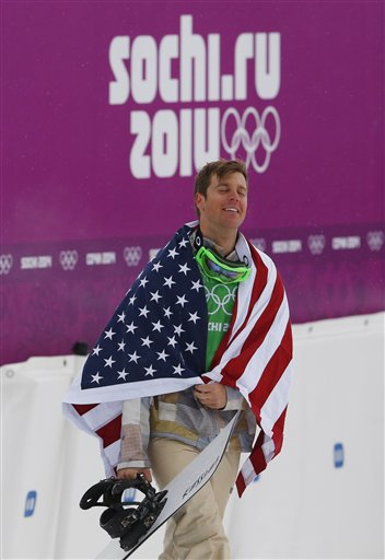 Bronze medalist Alex Deibold of the United States walks to a flower ceremony after the men's snowboard cross final at the Rosa Khutor Extreme Park, at the 2014 Winter Olympics, Tuesday, Feb. 18, 2014, in Krasnaya Polyana, Russia.