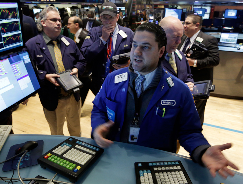Specialist Ronnie Howard, foreground, works at a post on the floor of the New York Stock Exchange on Wednesday. The market had its best day of the year Thursday.