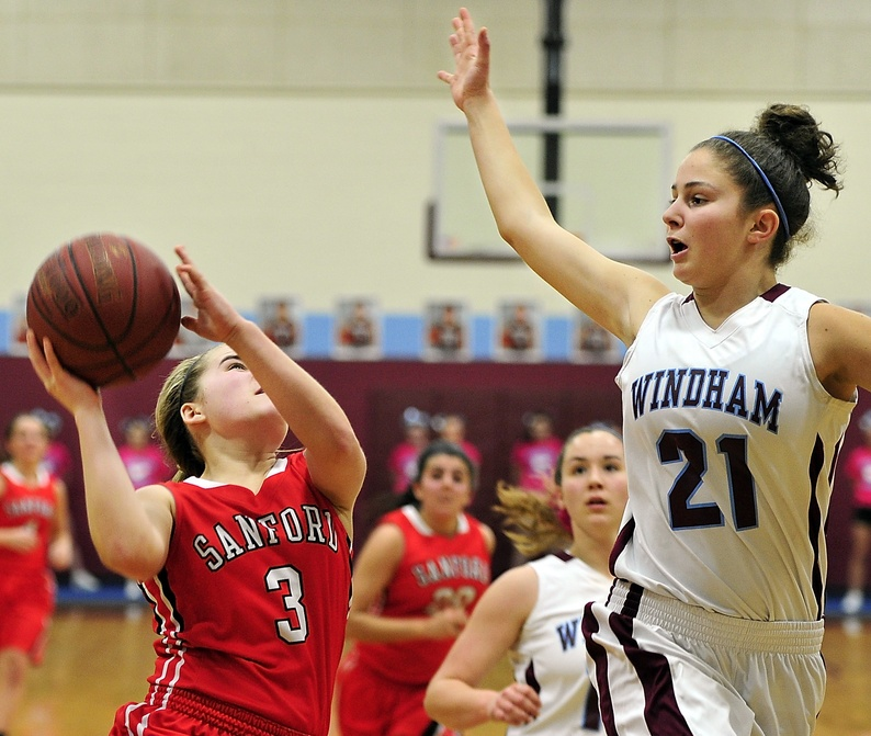Sanford No. 3, Summer Camire, drives to the basket against the defense of Windham No. 21, Luisa Sbardella, who blocks the shot as Windham hosts Sanford in girls high school basketball playoff action Wednesday. Gordon Chibroski/Staff Photographer. Wednesday, February 12, 2014 86087