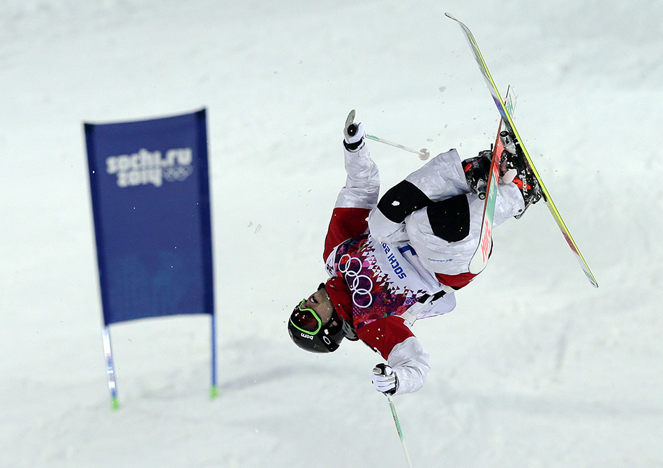 Canada's Alex Bilodeau jumps during the men's moguls qualifying at the Rosa Khutor Extreme Park at the 2014 Winter Olympics, Monday, Feb. 10, 2014, in Krasnaya Polyana, Russia.