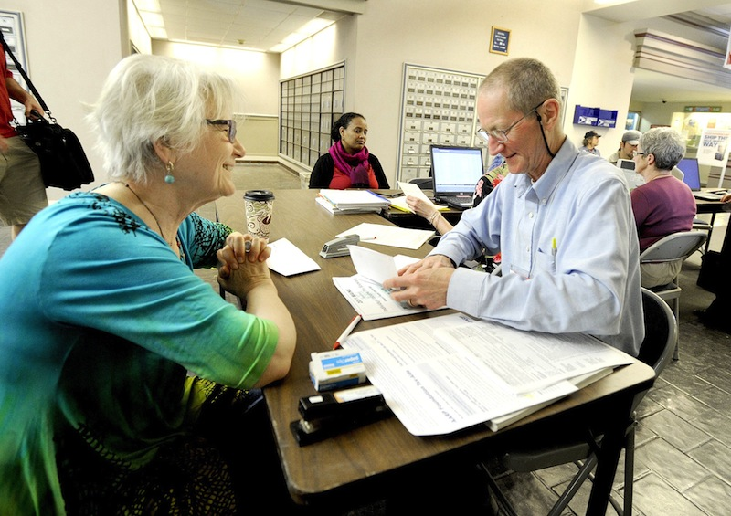In this 2012 file photo, RJ Harper (right), an IRS certified volunteer tax preparer, helps Ana Dana of South Portland at the Forest Avenue Post Office. Americans are getting bigger tax refunds in 2014, averaging more than $3,000 so far.