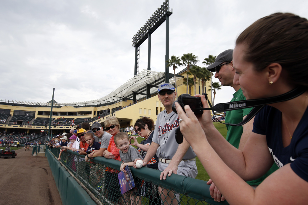 Emily Frederick, right, takes a picture of husband Brendt Frederick, wearing white-rimmed sunglasses, and son Parker Frederick, 2, before a spring training baseball game in Kissimmee, Fla., on Wednesday. After a long, cold winter, Americans across the winter-weary Midwest and the East Coast are desperate to escape.