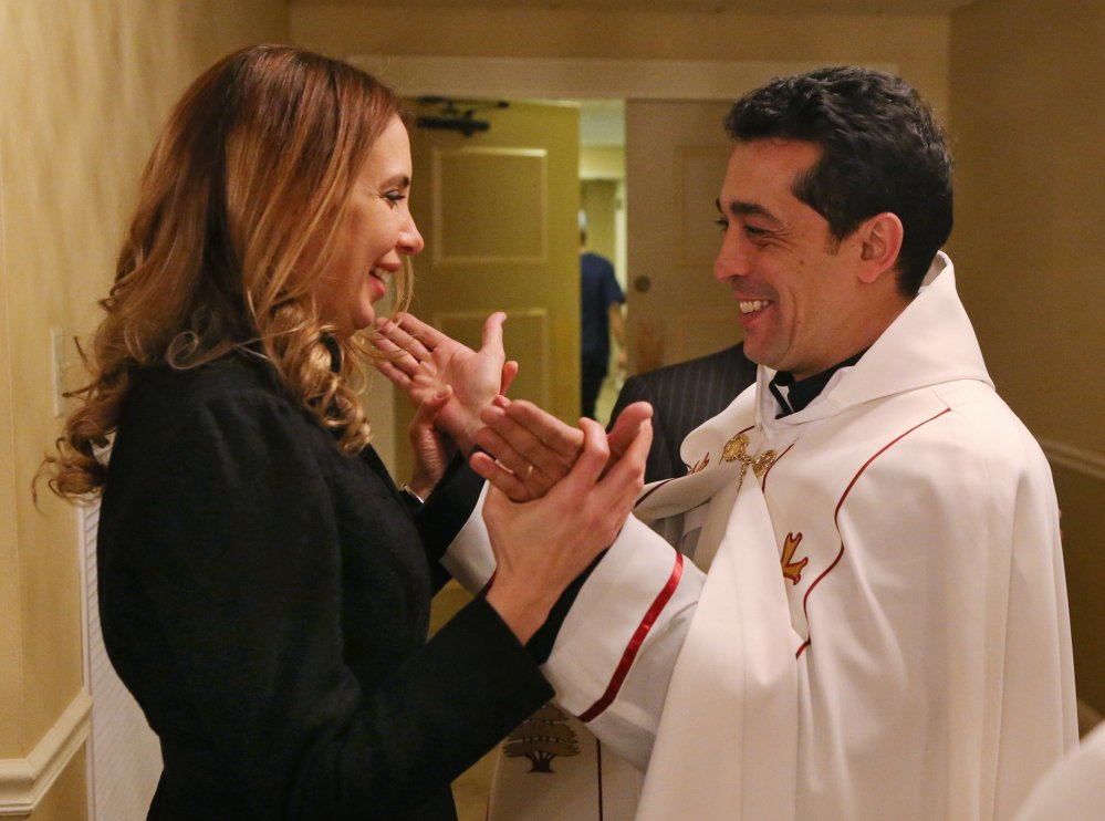 Manal Akiki greets her husband, Wissam Akiki, after his ordination as a priest in the Maronite Catholic Church at St. Raymond's Cathedral in St. Louis on Thursday. It was the first time in almost a century that a married Maronite priest has been ordained in the U.S.