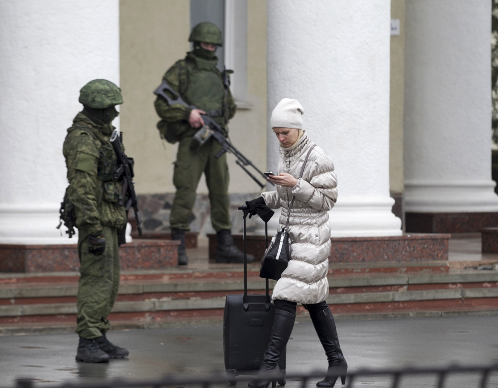 A woman walks past armed men at the Simferopol airport in the Crimea region on Friday. Armed men took control of two airports in the Crimea region, raising tensions with the West.