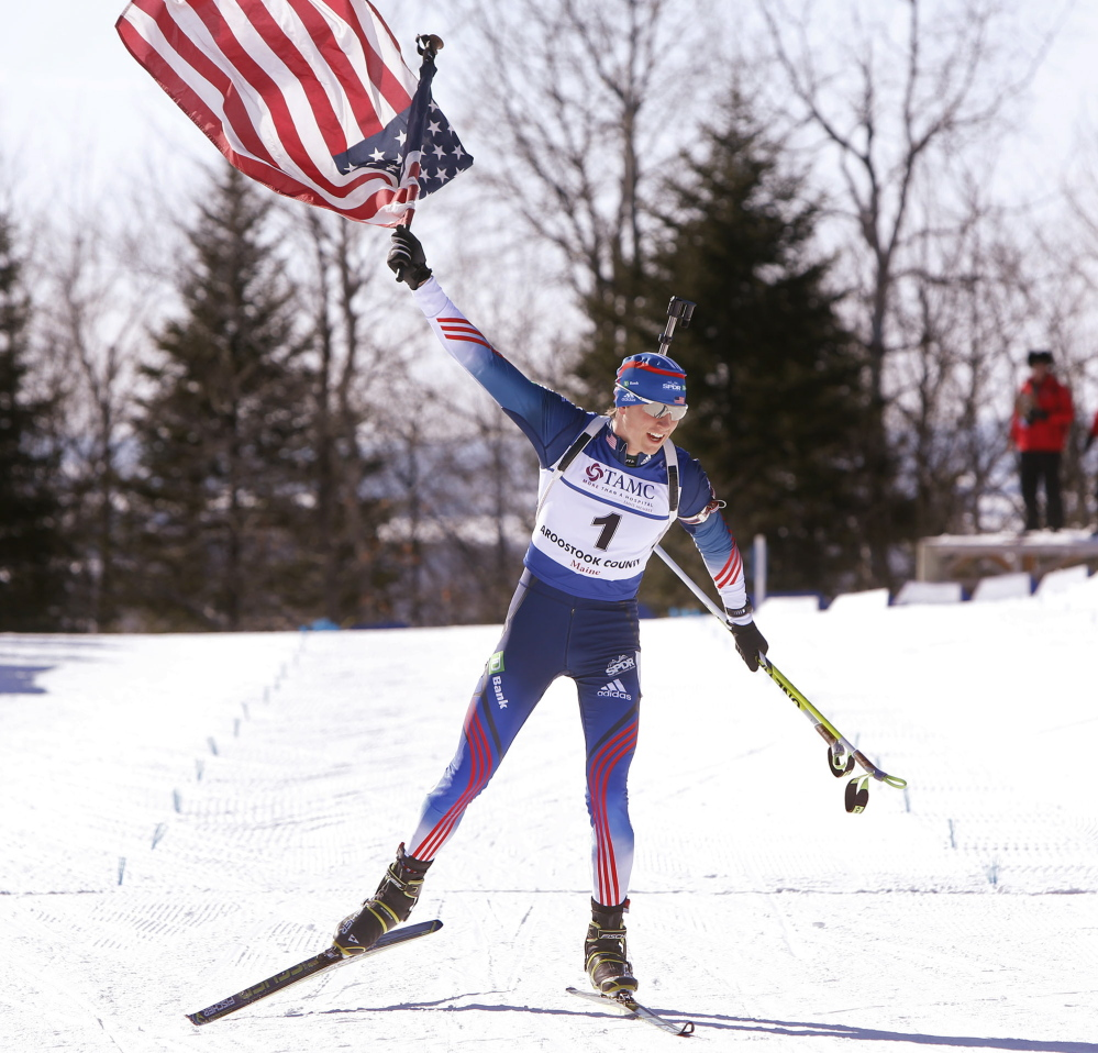 Sean Doherty of Center Conway, N.H., hoists the American flag high as he crosses the finish line to win the youth 10K pursuit Sunday at the IBU Biathlon Youth/Junior World Championships in Presque Isle, earning his second gold medal in three days.