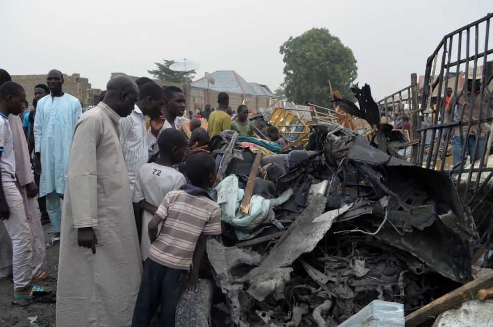 People gather to look at the remains of a car Sunday, after two car bombs exploded in Maiduguri, Nigeria, on Saturday night.