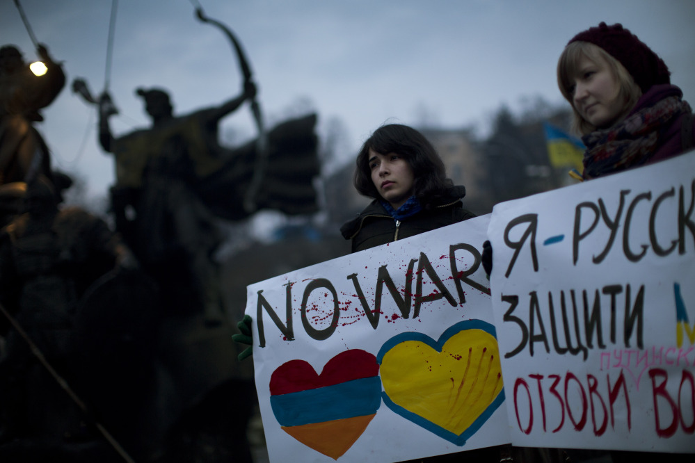 "Ukrainians Maria, 23, right, and Vanui, 22, hold posters against Russia's military intervention in Crimea, in Kiev, Ukraine, on Sunday. The poster on the right side reads in Ukrainian: ""I am from Russia, please protect me and remove the weapons and soldiers from Ukraine."""