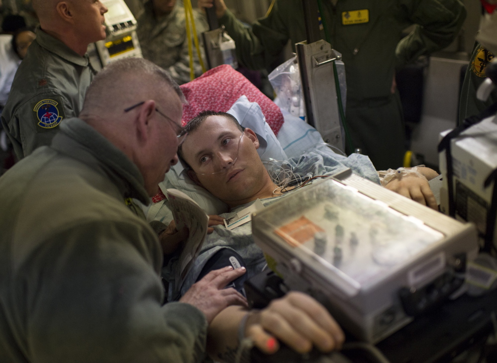 Marine Lance Cpl. Paul Shupert, 22, waits to be carried off the C-17 after its arrival at Andrews Air Force Base in Maryland. He lost part of a leg after stepping on a land mine in Afghanistan's Helmand province in November.
