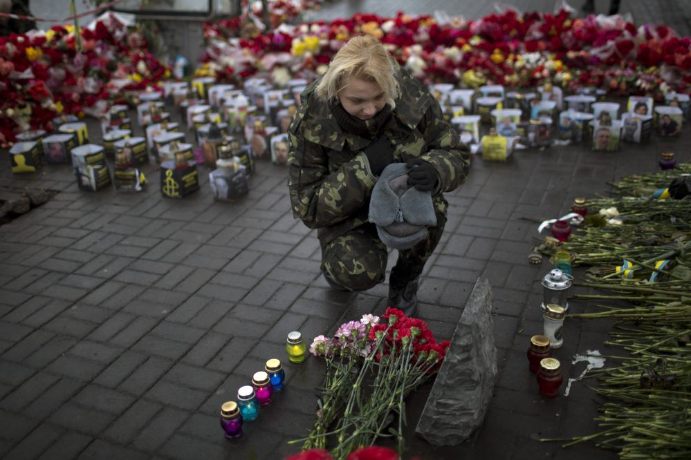 "An Ukrainian woman wearing camouflage uniform pays respect at the site were her friend Ustim Golodniuk was killed in clashes with the police at the Shrine of the Fallen in Kiev's Independence Square, Ukraine, Wednesday, March 5, 2014. The Shrine of the Fallen, located on Institutska Street, honors the fallen ""Heroes"" of the ""Heavenly Sotnya"" (Hundred). Over the course of the Euro Maidan protests, almost 100 protesters were killed by police."