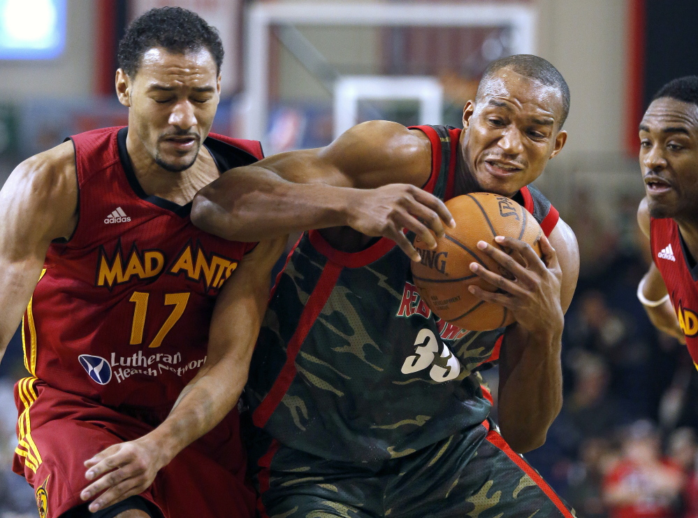 Chris Wright of the Maine Red Claws, center, powers his way past Fort Wayne defenders Sadiel Rojas, left, and Jamaal Franklin, right, Thursday at the Portland Expo. The Red Claws were wearing camoflage uniforms in honor of military appreciation day.