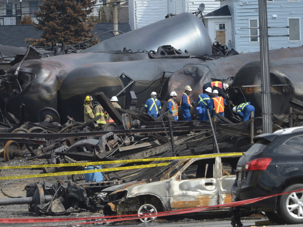 Emergency workers examine the aftermath of a train derailment and fire in Lac-Megantic, Quebec, in July. The Transportation Safety Board of Canada has released its analysis of the train's cargo.