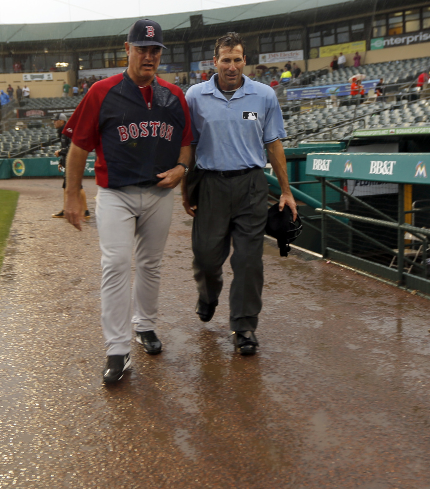 Boston Manager John Farrell and umpire Angel Hernandez leave the Jupiter, Fla., field after heavy rain in the eighth inning ends a scoreless exhibition game.