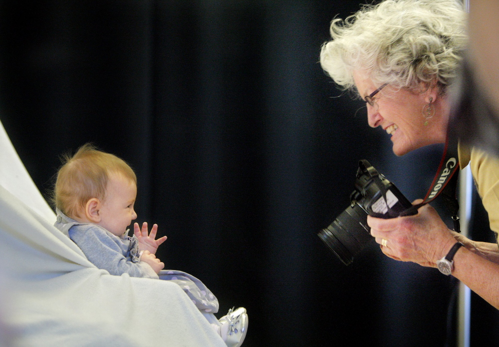 Photographer Jane Page-Conway gets a smile from 4-month-old Eva Dae Michaels of Falmouth during a 2012 casting call in Portland for announcements promoting the Harold Alfond College Challenge. The Harold Alfond Foundation will now automatically award a $500 Alfond college grant to all Maine babies, instead of making the college savings accounts an option.