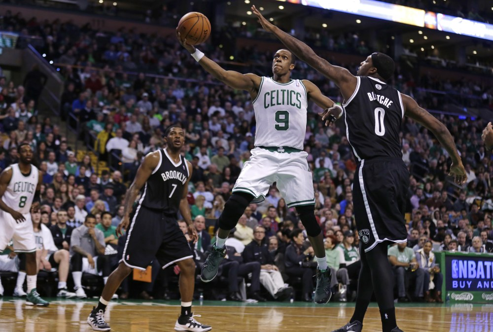 Celtics guard Rajon Rondo drives to the basket between Brooklyn's Joe Johnson, left, and Andray Blatche during Boston's 91-84 win Friday night