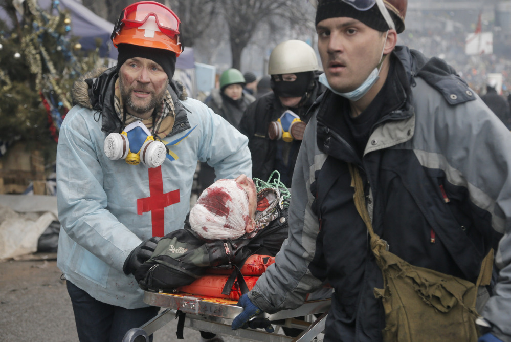 Activists evacuate a wounded protester during clashes with police in Kiev's Independence Square on Feb. 20. An investigation is trying to determine who was behind attacks by rooftop snipers.