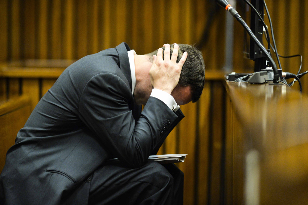 Oscar Pistorius cradles his head in his hands in court on the fifth day of his trial Friday in Pretoria, South Africa. A former girlfriend testified that on one occasion he fired his gun out of a car's sunroof soon after a policeman stopped him for speeding.