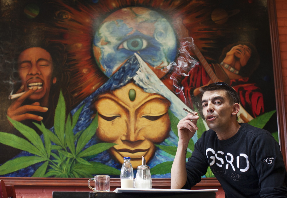A man smokes a joint in a coffee shop in the Netherlands, the world pioneer in pot liberalization. The country has recently taken a harder line toward marijuana, with mixed results seen particularly in border towns.