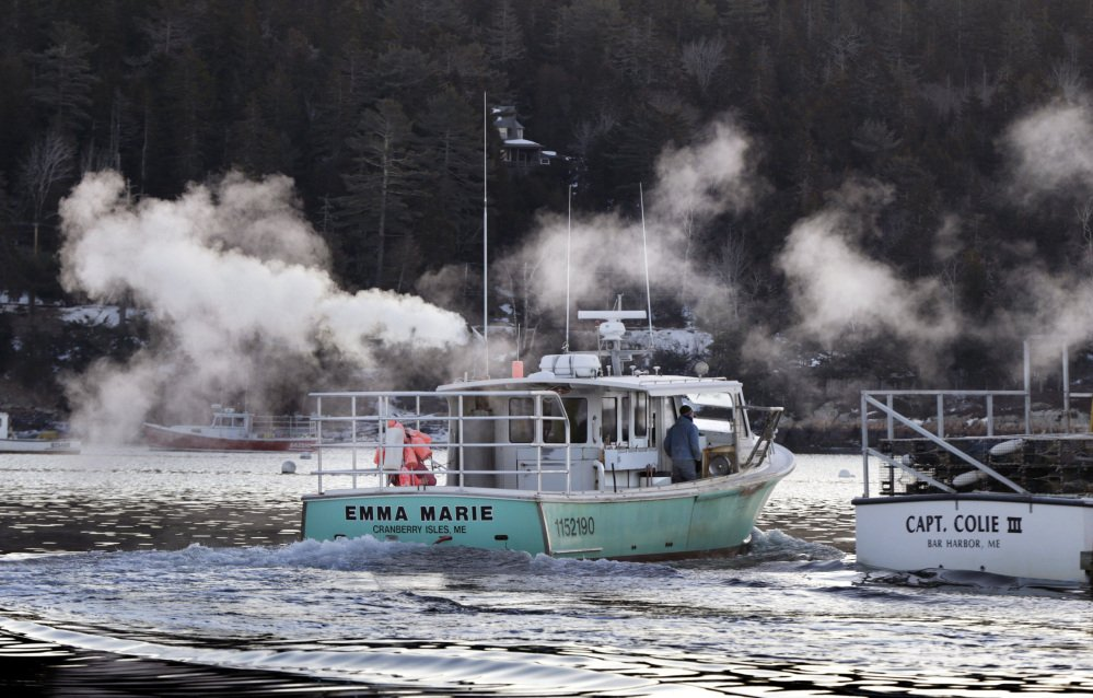 Boat exhaust rises as lobsterman Mark Fernald heads out from Northeast Harbor on Friday morning. The official beginning of spring is less than two weeks away, but temperatures still remain in the low teens at dawn.