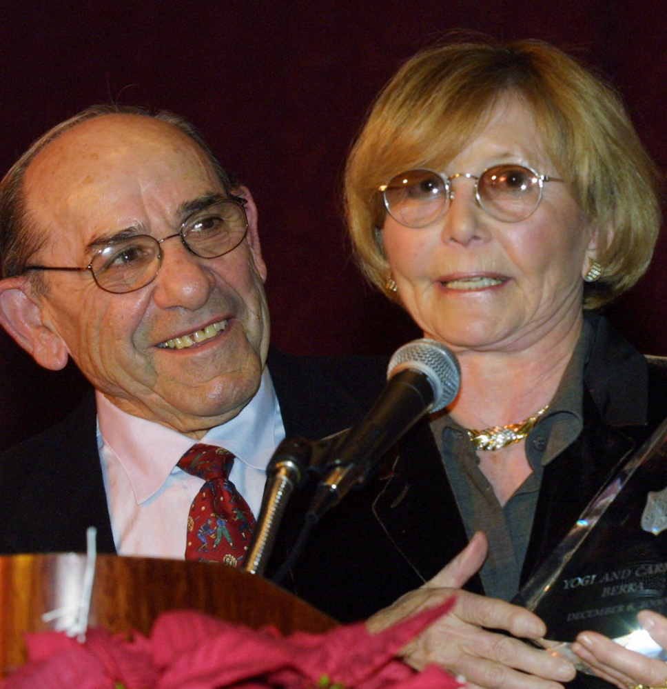 Baseball Hall-of-Famer Yogi Berra listens as his wife, Carmen, accepts the Pinnacle of Achievement award from the Salvation Army Association of Greater New York in 2000. She died Thursday at age 85.