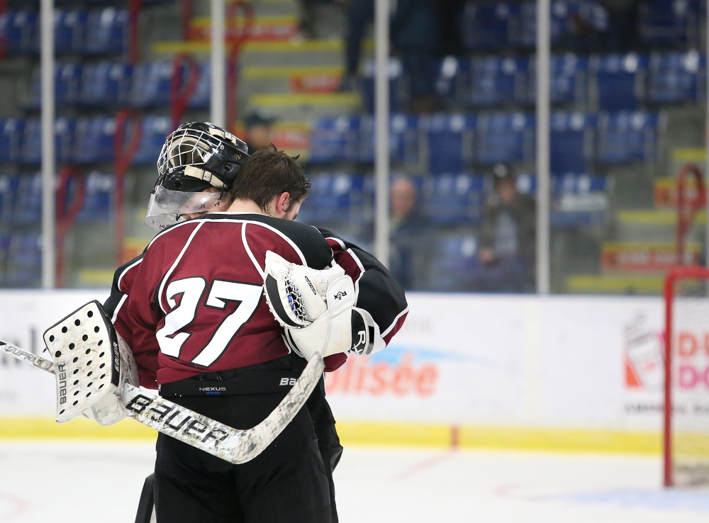 Justin Broy of Gorham embraces teammate Jared Wood after they lost 6-1 to Messalonskee in the Class B boys' hockey state championship game Saturday at the Colisee in Lewiston.