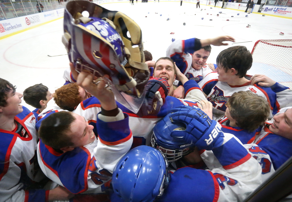 Messalonskee teammates mob their goalie Benjamin Weeks, center, as teammate Tyler Simpson, left, raises up his helmet after they defeated Gorham 6-1 in the Class B state championship on Saturday at the Colisee in Lewiston.