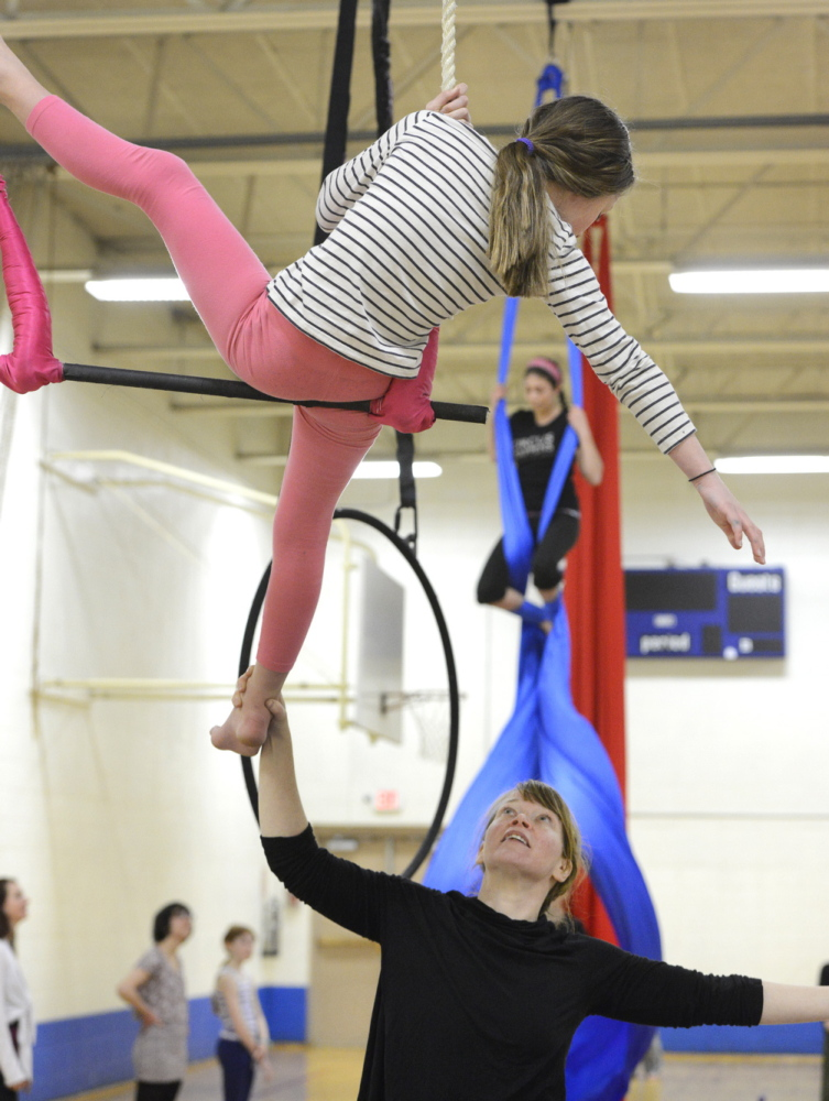 Aerials coach Jeanette Fertig works with Norah Peabey, 8, of Portland on the trapeze during Circus Atlantic's open house at Reiche Community School in Portland on Saturday.