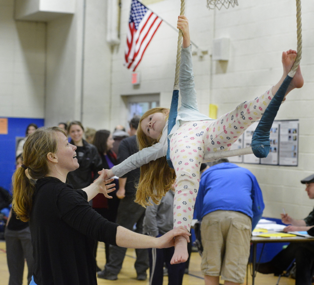 Aerials coach Jeanette Fertig works with Norah Peabey, 8, of Portland on the trapeze during Circus Atlantic's an open house at Reiche Community School in Portland on Saturday.