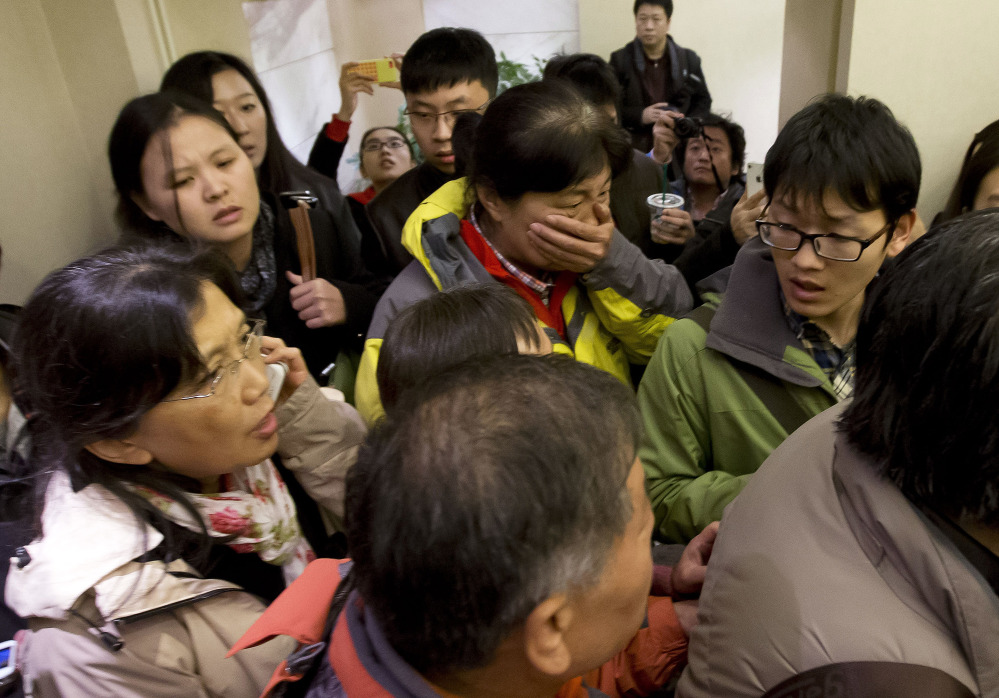 A woman, surrounded by members of the media, arrives at a hotel prepared for relatives and friends of passengers aboard a missing airplane, in Beijing on Saturday.