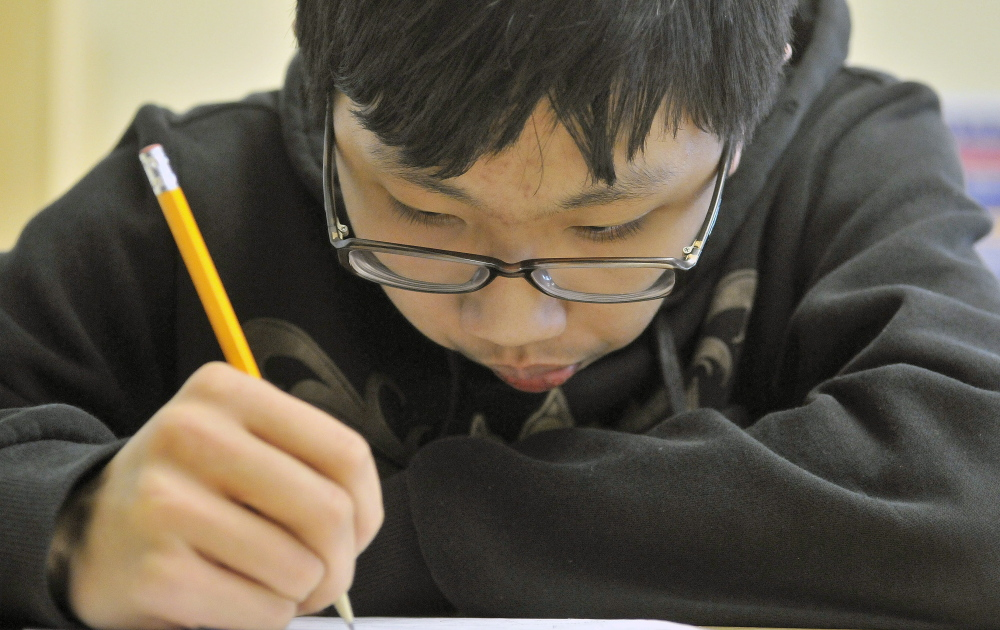 Eric Lu, 15, works through a mathematics problem Wednesday during Waterville Math Team practice at Waterville Senior High School. The team of mathletes has grown from six to 16 in about a year and a half.