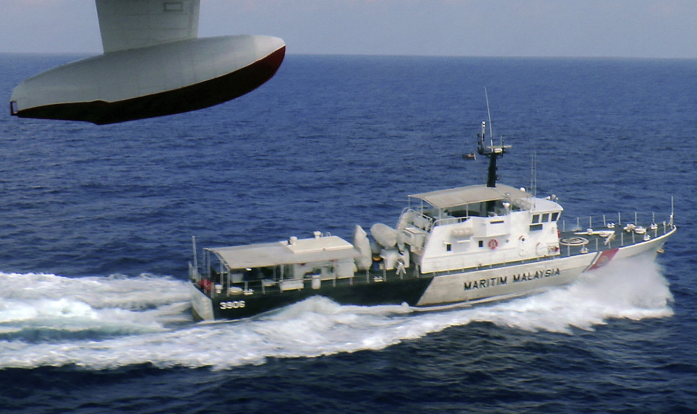 In this photo released by Malaysian Maritime Enforcement Agency, a patrol vessel of Malaysian Maritime Enforcement Agency searches for the missing Malaysia Airlines plane off Tok Bali Beach in Kelantan, Malaysia, Sunday.