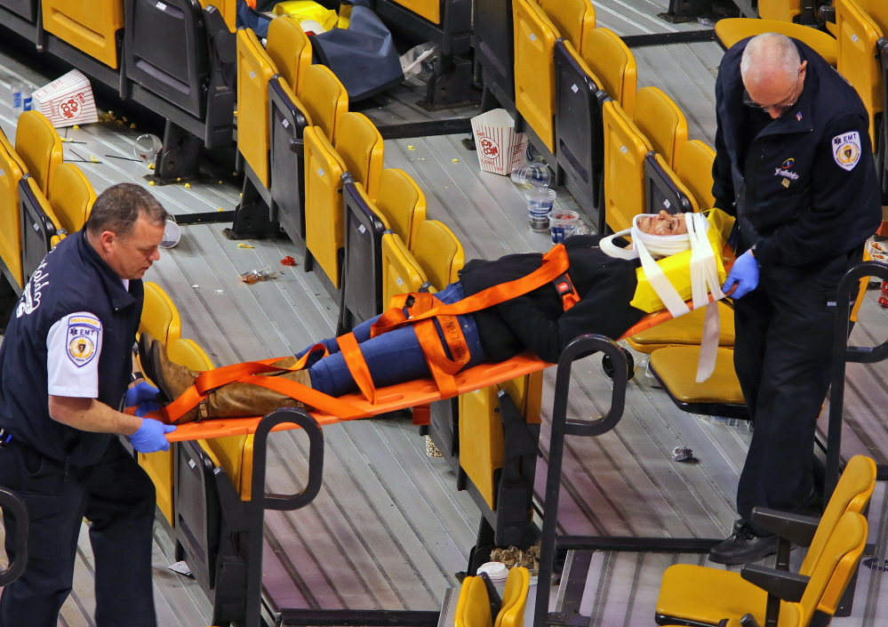 Emergency workers carry Sabina Grasso on a stretcher after a pole fell in TD Garden knocking Grasso unconscious.
