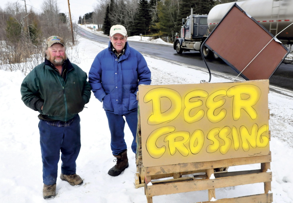 """SLOW DOWN: Ed Picard, left, and Lenny Cabral beside a sign that warns motorists that 14 recent collisions with deer have occurred recently along Route 139 near the Unity and Unity Township municipal boundary. """"People need to slow down,"""" Picard said. Cabral added the deer are active because they are hungry."""