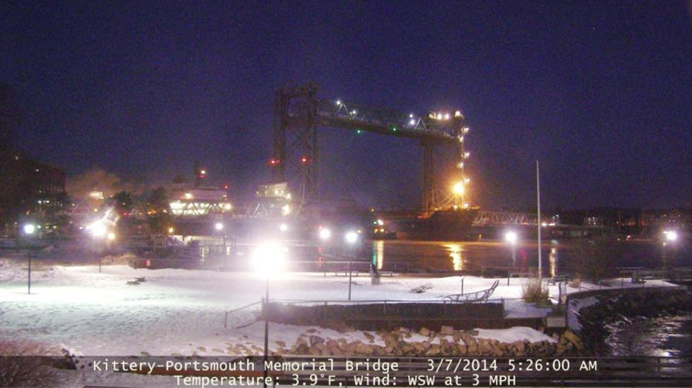 This image provided by the New Hampshire Department of Transportation shows the Seapride – its bow visible beneath the yellow light to the right of center in the photo – resting against a pier of the Memorial Bridge at 5:26 a.m. last Friday.