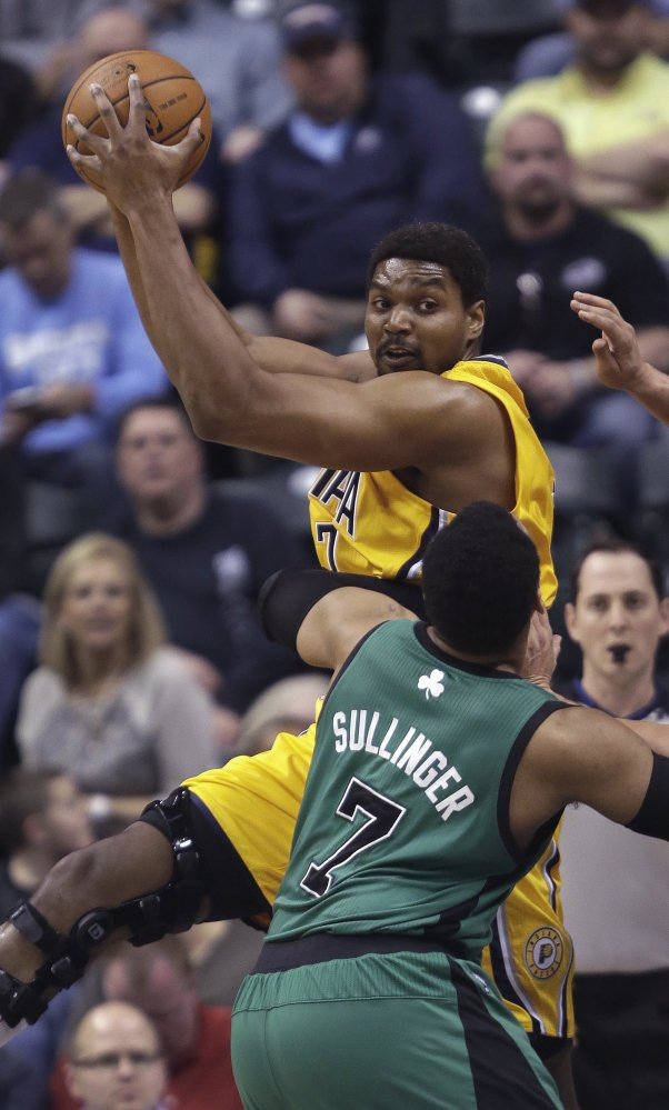 Andrew Bynum of the Indiana Pacers pulls down one of his 10 rebounds Tuesday night in front of Jared Sullinger of the Boston Celtics during the first half of the Pacers' 94-83 victory.