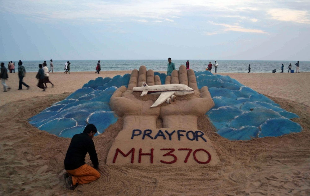 Sand artist Sudarshan Pattnaik creates a sculpture depicting the missing Malaysian Airlines aircraft on the beach in Puri, India, Wednesday, March 12, 2014. Malaysia has asked for India's assistance in searching for the missing Boeing 777 jetliner to widen the search to an area near the Andaman Sea, an Indian official said Wednesday.