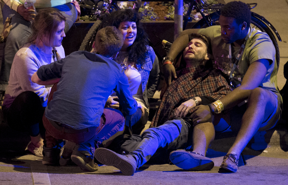 Unidentified people are comforted after being struck by a vehicle on Red River Street in downtown Austin, Texas, during SXSW late Wednesday.