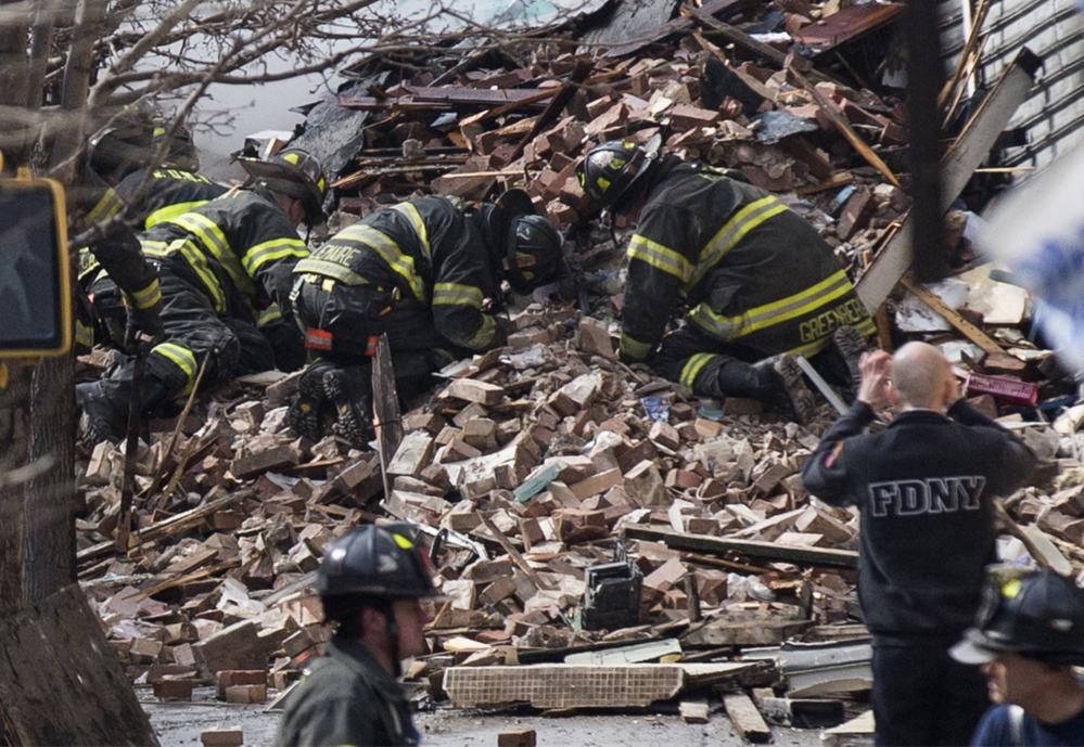 New York City firefighters dig through the rubble of a building explosion and collapse in East Harlem on Wednesday. Two apartment buildings collapsed, killing at least seven.