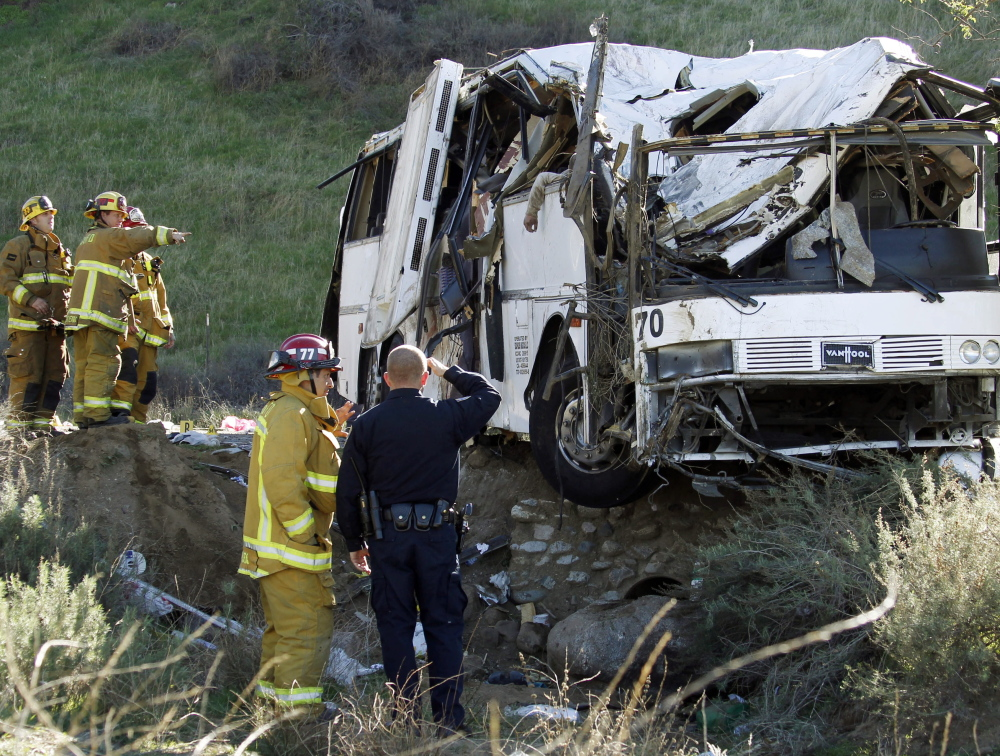 Rescue personnel survey the scene of a February tour bus crash north of Yucaipa, Calif., in which eight people died. The U.S. wants to require commercial vehicles to carry electronic devices to record drivers' hours behind the wheel, to make sure they don't drive tired.