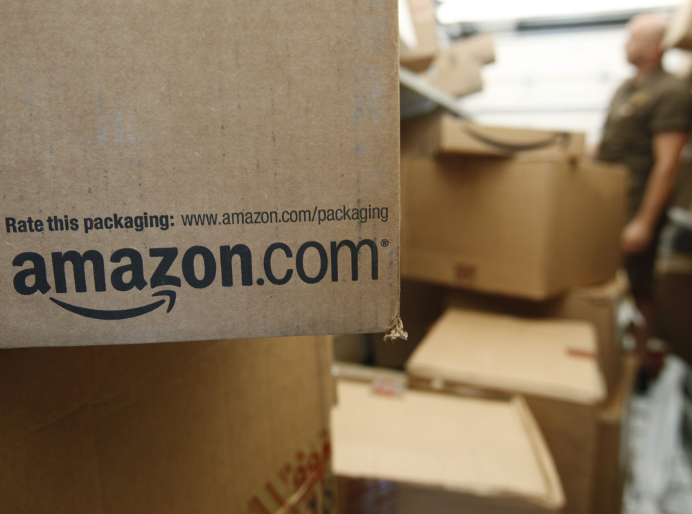 An Amazon.com package awaits delivery by UPS in Palo Alto, Calif. Amazon is raising the price of its popular Prime shipping and streaming video service to $99 per year, while also improving its selection of TV shows and movies.